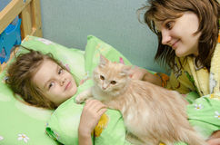 Gatto sveglio della figlia e della mamma di mattina Fotografia Stock