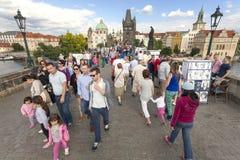 Gatuförsäljare och turist som går på Charles Bridge Royaltyfria Bilder