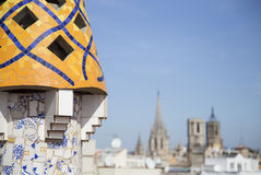 Gaudi chimney and view of Barcelona Cathedral. Barcelona, Spain - September 25, 2015: Gaudi Chimney, Palau Guell, Gaudi broken tile mosacis and strange decorated Royalty Free Stock Image