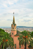 Gaudi house with tower in Park Guell, Barcelona. Last home of Gaudi surrounded by palm trees, in Park Guell, with high cityscape view of Barcelona, Spain Royalty Free Stock Images