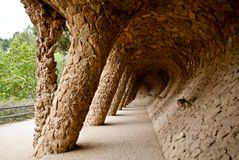 Gaudi's colonnaded footpath. Colonnaded footpath under the roadway viaduct in Park Guell, with external columns sloping to take the diagonal thrust from the Stock Image