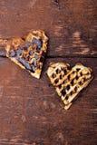 Gaufre deux en forme de coeur belge avec du chocolat sur le fond en bois Configuration plate Copiez l'espace Images stock