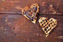 Gaufre deux en forme de coeur belge avec du chocolat sur le fond en bois Configuration plate Copiez l'espace Photographie stock