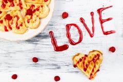 Gaufre en forme de coeur belge sur le fond blanc Amour de Word fait par la confiture Image stock