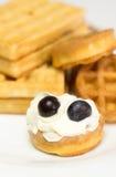 Gaufre ronde avec de la crème et des myrtilles sur un fond de plat, Photographie stock libre de droits