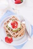 Gaufres avec de la farine et des fruits de blé entier d'un plat blanc Photo libre de droits