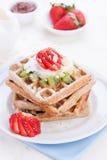 Gaufres avec de la farine et des fruits de blé entier d'un plat blanc Photos libres de droits