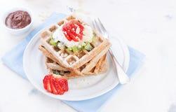 Gaufres avec de la farine et des fruits de blé entier d'un plat blanc Photo stock