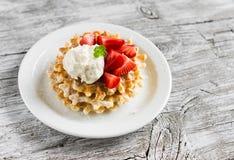 Gaufres avec de la glace à la vanille et des fraises d'un plat blanc Images stock