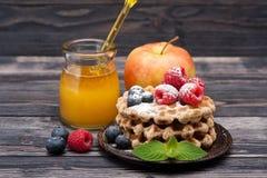 Gaufres avec des framboises, des myrtilles, le fruit et le miel Photo libre de droits