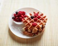 Gaufres avec du miel, la confiture, et les baies d'un plat blanc Photo stock