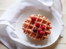 Gaufres avec du miel, la confiture, et les baies d'un plat blanc Photos libres de droits