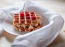 Gaufres avec du miel, la confiture, et les baies d'un plat blanc Photographie stock