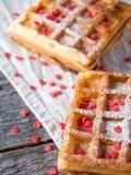 Gaufres belges viennoises molles avec du sucre en poudre et les coeurs rouges sur le fond en bois rustique Photographie stock