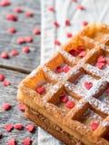 Gaufres belges viennoises molles avec du sucre en poudre et les coeurs rouges sur le fond en bois rustique Photo stock
