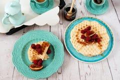 Gaufres en forme de coeur belges molles avec des framboises et des figues, couvertes du miel du plat de bleu de turquoise Photo stock