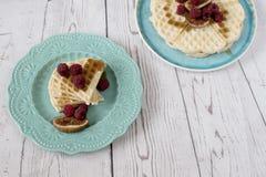 Gaufres en forme de coeur belges molles faites maison avec des framboises et des figues, couvertes du miel du plat de bleu de tur Photo libre de droits