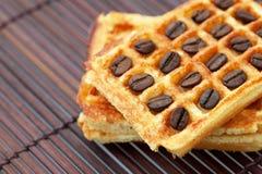 Gaufres et grains de café sur un couvre-tapis en bambou Image stock