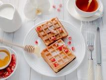 Gaufres viennoises appétissantes délicieuses avec des graines de miel et de grenade d'un plat blanc, fond en bois clair Photos stock