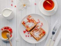 Gaufres viennoises appétissantes délicieuses avec des graines de miel et de grenade d'un plat blanc, fond en bois clair Photographie stock