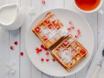 Gaufres viennoises appétissantes délicieuses avec des graines de miel et de grenade d'un plat blanc, fond en bois clair Image libre de droits