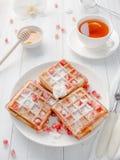 Gaufres viennoises appétissantes délicieuses avec des graines de miel et de grenade d'un plat blanc, fond en bois clair Images libres de droits