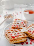 Gaufres viennoises appétissantes délicieuses avec des graines de miel et de grenade d'un plat blanc, fond en bois clair Images stock