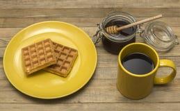 Gaufres viennoises avec du café de tasse et le miel de pot Images stock