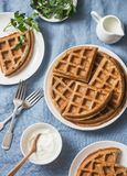 Gaufres viennoises, crème et lait de petit déjeuner savoureux de blé entier sur le fond bleu Photo stock