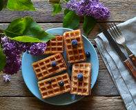 Gaufrettes avec des myrtilles et des lilas sur une table en bois Photo stock