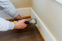Gauge Finish Nailer man nailed slats custom house molding contractor up a wall section for luxury Stock Image