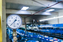 Gauge for mBar measurement with blurred industrial background Stock Image