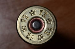 12-gauge shotgun shell. On a brown background Royalty Free Stock Photography