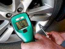 Gauging Nitrogen Ratio (%) in a Passenger Car Tire. Checking the nitrogen (N2) ratio, or percentage, in a passenger car tire with a nitrogen analyzer Royalty Free Stock Photo