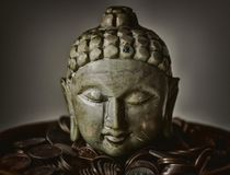 Gautama Buddha Bust Surrounded by Coins royalty free stock photos