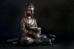 Gautama Buddha de bronze com as rochas escuras isoladas no preto imagem de stock