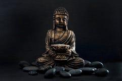 Gautama Buddha de bronze com as rochas escuras isoladas no preto imagens de stock