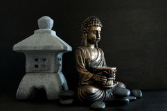 Gautama Buddha de bronze e templo diminuto com as rochas escuras isoladas no preto fotografia de stock