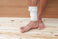 Gauze bandage the foot treating patient  male. Gauze bandage the foot treating patient ulcers male is wrap his injury, on wooden floor background Royalty Free Stock Photography