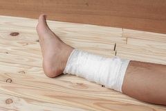 Gauze bandage the foot treating patient  male. Gauze bandage the foot treating patient ulcers male is wrap his injury, on wooden floor background Stock Photos