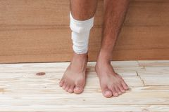 Gauze bandage the foot treating patient  male. Gauze bandage the foot treating patient ulcers male is wrap his injury, on wooden floor background Stock Images