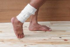 Gauze bandage the foot treating patient  male. Gauze bandage the foot treating patient ulcers male is wrap his injury, on wooden floor background Stock Image