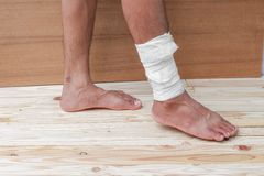 Gauze bandage the foot treating patient  male. Gauze bandage the foot treating patient ulcers male is wrap his injury, on wooden floor background Royalty Free Stock Photos