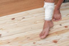Gauze bandage the foot treating patient  male. Gauze bandage the foot treating patient ulcers male is wrap his injury, on wooden floor background Stock Photo
