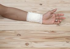 Gauze bandage the hand contusion. treating patients with hand. With a wrist left, male With gauze is wrapping his injury On a wooden table . select focus front Royalty Free Stock Photography