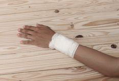 Gauze bandage the hand contusion. treating patients with hand. With a wrist left, male With gauze is wrapping his injury On a wooden table . select focus front Stock Photography