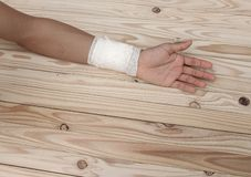 Gauze bandage the hand contusion. treating patients with hand. With a wrist left, male With gauze is wrapping his injury On a wooden table . select focus front Royalty Free Stock Photos