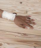Gauze bandage the hand contusion. treating patients with hand. With a wrist left, male With gauze is wrapping his injury On a wooden table . select focus front Royalty Free Stock Photo