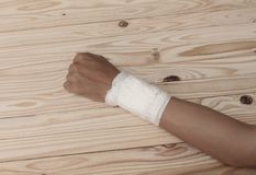 Gauze bandage the hand contusion. treating patients with hand. With a wrist left, male With gauze is wrapping his injury On a wooden table . select focus front Stock Images