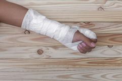Gauze bandage the hand contusion. treating patients with hand. With a wrist left, male With gauze wrapping his injury On a wooden table . select focus front Stock Images